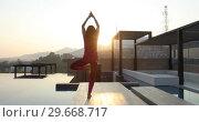 Купить «Anonymous female doing yoga on roof», видеоролик № 29668717, снято 8 января 2019 г. (c) Ekaterina Demidova / Фотобанк Лори