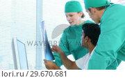 High angle of medical team examining an xray. Стоковое видео, агентство Wavebreak Media / Фотобанк Лори