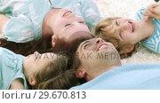 Купить «Family Lying on the ground looking at camera», видеоролик № 29670813, снято 9 октября 2009 г. (c) Wavebreak Media / Фотобанк Лори