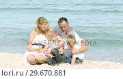 Купить «Happy family sitting on the beach», видеоролик № 29670881, снято 13 октября 2009 г. (c) Wavebreak Media / Фотобанк Лори