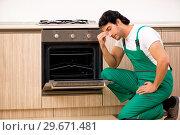 Купить «Young contractor repairing oven in kitchen», фото № 29671481, снято 31 октября 2018 г. (c) Elnur / Фотобанк Лори