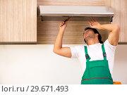 Купить «Young contractor repairing air-conditioner in kitchen», фото № 29671493, снято 31 октября 2018 г. (c) Elnur / Фотобанк Лори