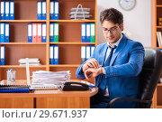 Купить «Young employee working in the office», фото № 29671937, снято 9 августа 2018 г. (c) Elnur / Фотобанк Лори
