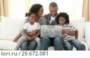 Купить «Panorama of AfroAmerican family using a laptop on the sofa», видеоролик № 29672081, снято 21 октября 2009 г. (c) Wavebreak Media / Фотобанк Лори
