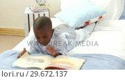 Купить «AfroAmerican smiling little boy reading in bed», видеоролик № 29672137, снято 21 октября 2009 г. (c) Wavebreak Media / Фотобанк Лори