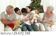 Купить «Family playing with Christmas gifts in the livingroom», видеоролик № 29672189, снято 20 октября 2009 г. (c) Wavebreak Media / Фотобанк Лори