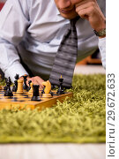 Купить «Young handsome boss playing chess during break», фото № 29672633, снято 10 сентября 2018 г. (c) Elnur / Фотобанк Лори