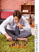 Купить «Young handsome boss playing chess during break», фото № 29672641, снято 10 сентября 2018 г. (c) Elnur / Фотобанк Лори