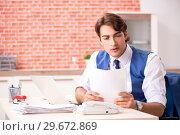 Купить «Young handsome employee working in the office», фото № 29672869, снято 12 сентября 2018 г. (c) Elnur / Фотобанк Лори