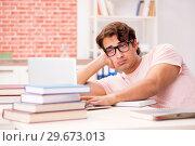 Купить «Young student preparing for college exams», фото № 29673013, снято 14 сентября 2018 г. (c) Elnur / Фотобанк Лори