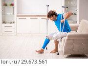 Купить «Leg injured young man with crutches at home», фото № 29673561, снято 19 сентября 2018 г. (c) Elnur / Фотобанк Лори
