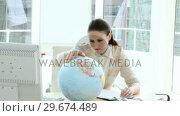 Купить «Pretty businesswoman looking at a terrestrial globe», видеоролик № 29674489, снято 17 февраля 2020 г. (c) Wavebreak Media / Фотобанк Лори