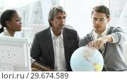 Купить «United business people looking at a terrestrial globe», видеоролик № 29674589, снято 8 декабря 2019 г. (c) Wavebreak Media / Фотобанк Лори