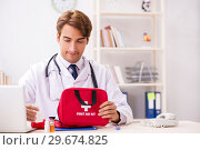 Купить «Young doctor with first aid kit in hospital», фото № 29674825, снято 23 августа 2018 г. (c) Elnur / Фотобанк Лори