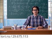 Купить «Young funny math teacher in front of chalkboard», фото № 29675113, снято 20 ноября 2018 г. (c) Elnur / Фотобанк Лори