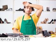 Купить «Young man repairing shoes in workshop», фото № 29675297, снято 22 октября 2018 г. (c) Elnur / Фотобанк Лори