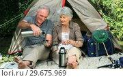 Aged couple drinking coffee sitting near a tent. Стоковое видео, агентство Wavebreak Media / Фотобанк Лори