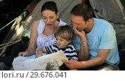 Купить «Family looking at a map near a tent», видеоролик № 29676041, снято 7 ноября 2010 г. (c) Wavebreak Media / Фотобанк Лори