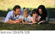 Купить «Family looking books and enjoying a good weather», видеоролик № 29676129, снято 10 ноября 2010 г. (c) Wavebreak Media / Фотобанк Лори