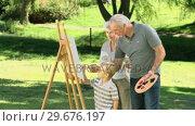 Grandparents and grandson painting a canvas. Стоковое видео, агентство Wavebreak Media / Фотобанк Лори