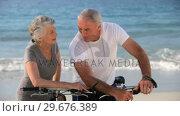 Aged couple with bikes talking each other. Стоковое видео, агентство Wavebreak Media / Фотобанк Лори