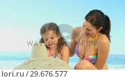 Купить «Beautiful mother playing with her daughter on the sand», видеоролик № 29676577, снято 14 ноября 2010 г. (c) Wavebreak Media / Фотобанк Лори
