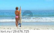 Купить «Woman holding her surfboard», видеоролик № 29676725, снято 15 ноября 2010 г. (c) Wavebreak Media / Фотобанк Лори