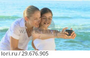 Mother and daughter and camera on a beach. Стоковое видео, агентство Wavebreak Media / Фотобанк Лори