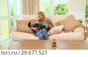 Купить «Young mother bottlefeeding her baby on sofa», видеоролик № 29677521, снято 6 ноября 2010 г. (c) Wavebreak Media / Фотобанк Лори