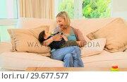 Купить «Young blonde woman bottlefeeding her baby on sofa», видеоролик № 29677577, снято 6 ноября 2010 г. (c) Wavebreak Media / Фотобанк Лори