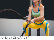 Купить «Blonde woman battling ropes during high intensive workout at the gym.», фото № 29677797, снято 6 сентября 2018 г. (c) Pavel Biryukov / Фотобанк Лори