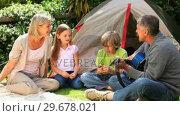 Купить «Family listening to the father playing guitar», видеоролик № 29678021, снято 6 ноября 2010 г. (c) Wavebreak Media / Фотобанк Лори