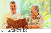 Retired couple looking at an album. Стоковое видео, агентство Wavebreak Media / Фотобанк Лори