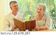 Купить «Mature couple reminiscing looking at an album », видеоролик № 29678281, снято 5 ноября 2010 г. (c) Wavebreak Media / Фотобанк Лори