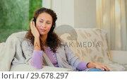 Купить «Young woman listening to music with headphones», видеоролик № 29678297, снято 5 ноября 2010 г. (c) Wavebreak Media / Фотобанк Лори