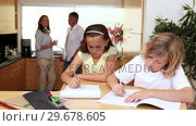 Brother and sister doing homework in the kitchen with parents behind them. Стоковое видео, агентство Wavebreak Media / Фотобанк Лори