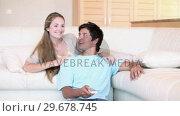 Купить «Video of a couple looking the TV», видеоролик № 29678745, снято 3 ноября 2011 г. (c) Wavebreak Media / Фотобанк Лори