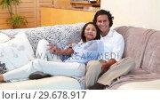 Купить «Couple watching TV», видеоролик № 29678917, снято 3 ноября 2011 г. (c) Wavebreak Media / Фотобанк Лори