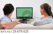 Купить «Couple looking at the television screen», видеоролик № 29679625, снято 4 ноября 2011 г. (c) Wavebreak Media / Фотобанк Лори