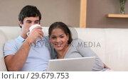 Купить «Happy couple looking at a laptop», видеоролик № 29679753, снято 4 ноября 2011 г. (c) Wavebreak Media / Фотобанк Лори