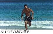Купить «Young man running in slow motion in shorts», видеоролик № 29680089, снято 15 ноября 2011 г. (c) Wavebreak Media / Фотобанк Лори