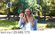 Купить «Blonde woman in slow motion blowing bubbles», видеоролик № 29680173, снято 16 ноября 2011 г. (c) Wavebreak Media / Фотобанк Лори