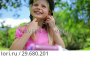 Купить «Girl puts on a pink cycling helmet and fastens the clasps», видеоролик № 29680201, снято 17 ноября 2011 г. (c) Wavebreak Media / Фотобанк Лори