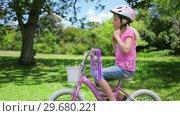 Купить «Girl puts on a cycling helmet and holds the handle bars», видеоролик № 29680221, снято 17 ноября 2011 г. (c) Wavebreak Media / Фотобанк Лори