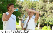 A couple take a break from training as they drink water and chat. Стоковое видео, агентство Wavebreak Media / Фотобанк Лори