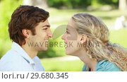 A couple look at each other as they kiss in the park and then look at the camera. Стоковое видео, агентство Wavebreak Media / Фотобанк Лори