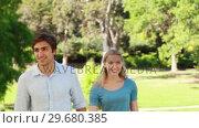 Купить «A couple walk towards the camera together and then laugh and wave into it», видеоролик № 29680385, снято 17 ноября 2011 г. (c) Wavebreak Media / Фотобанк Лори