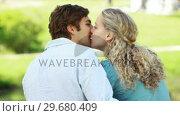 Купить «A man and woman sit in the park embraced as they kiss each other», видеоролик № 29680409, снято 17 ноября 2011 г. (c) Wavebreak Media / Фотобанк Лори