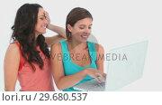 Купить «Two girls using a laptop», видеоролик № 29680537, снято 11 ноября 2011 г. (c) Wavebreak Media / Фотобанк Лори