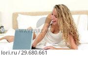 Купить «Blonde haired woman laughing while using a laptop», видеоролик № 29680661, снято 11 ноября 2011 г. (c) Wavebreak Media / Фотобанк Лори